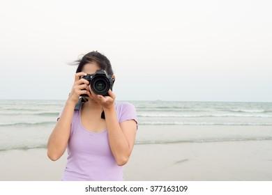 Beautiful girl takes a photograph