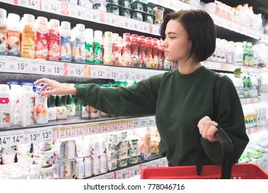 A beautiful girl takes a yogurt from the shelves of the milk department of the supermarket. Shopping in a supermarket.