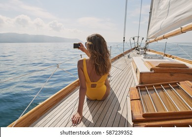 Beautiful girl taking photo on sailboat using smart phone technology for social media in ocean on luxury lifestyle adventure travel vacation