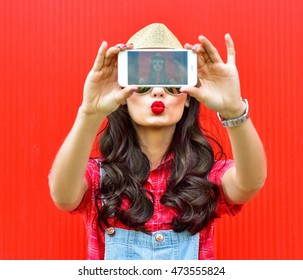 Beautiful girl taking photos on smartphone self-portrait, screen view, on a red background.