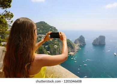 Beautiful girl taking picture in Capri Island with Faraglioni sea stack and blue crystalline water, Capri, Italy