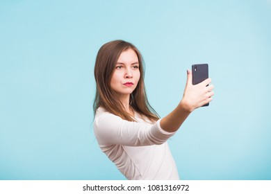 Beautiful girl taking selfie over blue background