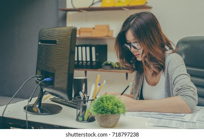 Beautiful girl taking write record from a computer down on paper, about what's interesting at her job.