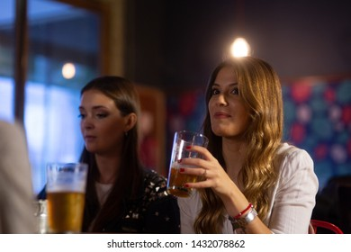 Beautiful girl talking with friends, having a good time in a bar.
