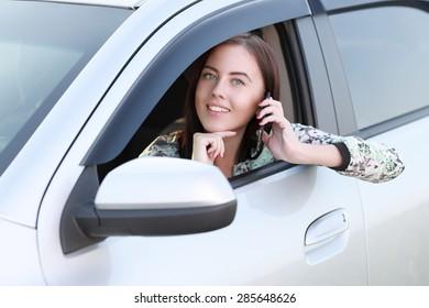 beautiful girl talking on phone in car