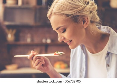 Beautiful girl is tasting food and smiling while cooking in kitchen at home