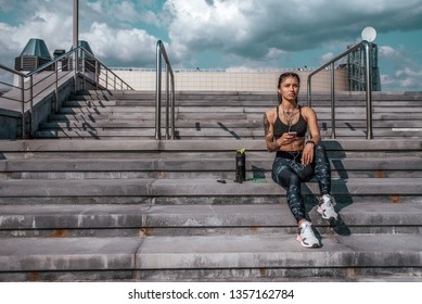 Beautiful girl tattoos, sitting summer city hand smartphone, listening music with headphones. Resting jogging workout. Concept motivation active life position, healthy lifestyle. Free space for text.