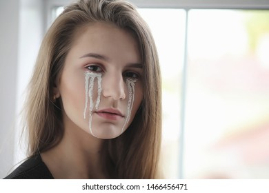 Beautiful girl with tears in eyes. Young girl with painted tears posing on camera. Girl for carnival with mask and makeup.