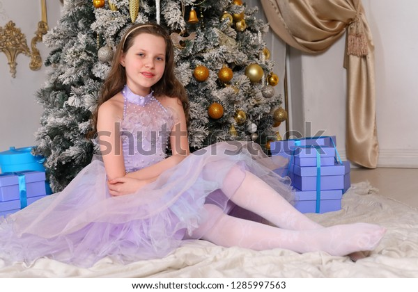 beautiful girl the teenager in a blue ball dress sits at a New Year tree and looks and touches New Year's toys and boxes with gifts and beautifully poses in studio and smiles