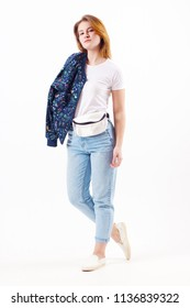 Beautiful girl teenager in bomber and jeans poses in white studio, full body