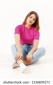 Beautiful girl teenager in pink t-shirt and jeans sits on floor in white studio, full body