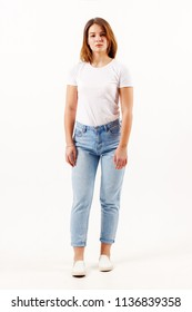 Beautiful girl teenager in white t-shirt and jeans poses in white studio