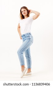 Beautiful girl teenager in white t-shirt and jeans poses in white studio, full body