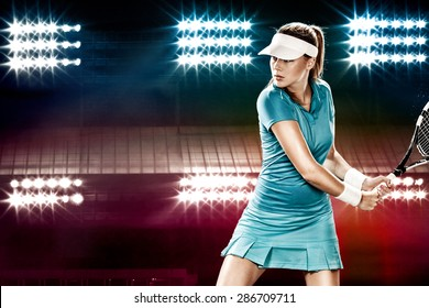 Beautiful girl tennis player with a racket on dark background wiht lights