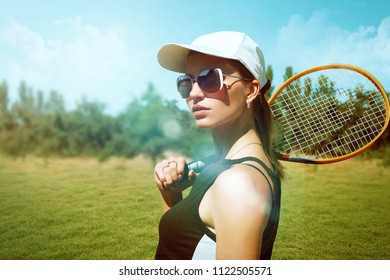 Beautiful girl with a tennis racket on a nature background