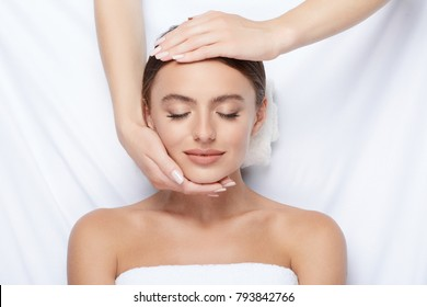 Beautiful girl with thick eyebrows and perfect skin doing facial massage at  white background, beauty photo concept, hands on face, skin care, smiling.