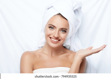 Beautiful  girl with thick eyebrows and perfect skin at white background, towel on head, beauty photo concept, skin care, spa concept, holding product and smiling.