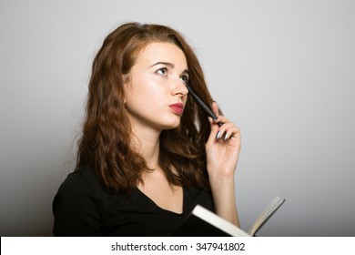 beautiful girl thought with a notebook and pen, office manager concept shot isolated on gray background