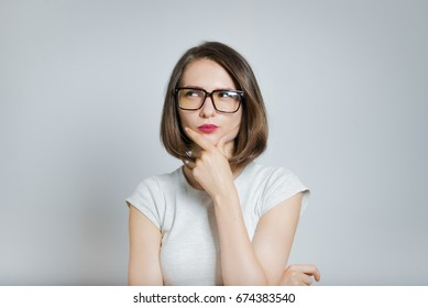 Beautiful girl thoughtful, wearing glasses, isolated on gray background