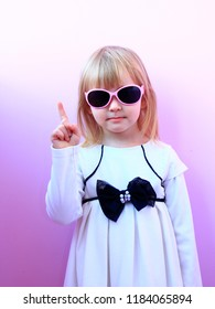 Beautiful girl threatening finger. Young serious girl shaking her finger. Little girl in sunglasses and nice dress threatening finger. Angry child. Girl wagging her index finger warning someone