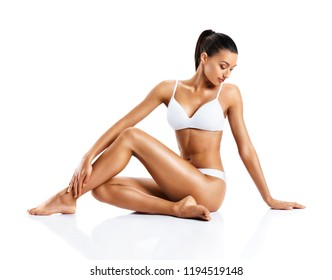 Beautiful girl touching her healthy skin. Photo of young girl sitting on white background. Beauty and body care concept