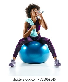 Beautiful girl with towel and bottle of water sitting on gymnastic ball. Photo of african fitness girl isolated on white background. Health concept.