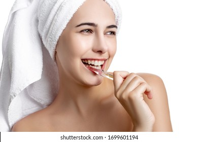 beautiful girl with a towel on her head brushes her teeth and toothpaste