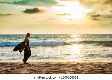 Beautiful girl in traditional clothes (sari) walks along the deserted tropical sandy beach of the ocean. Fresh breeze and palms.