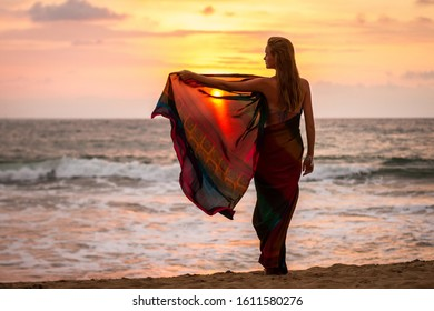 Beautiful girl in traditional clothes (sari) on the deserted tropical sandy beach of the ocean at sunset