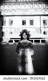 Beautiful girl in traditional Ukrainian costume posing in old town  b&w
