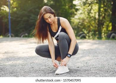 Beautiful girl training. Sports girl in a sportswear. Brunette in a black top