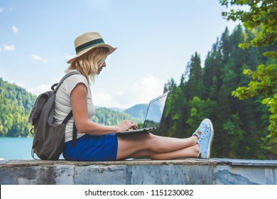 Beautiful girl traveler in a hat on a lake with a laptop