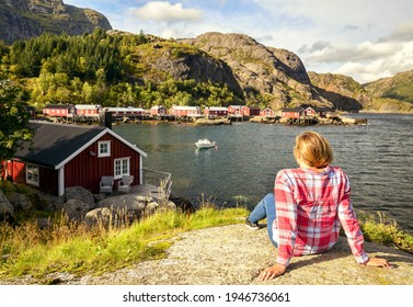 Beautiful girl traveler sitting on a rock on the background of traditional red rorbu traveling to Lofoten in Norway