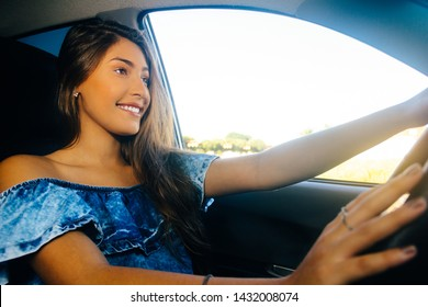 Beautiful girl traveling. She is inside the car, holding the steering wheel. She is smiling. Concept of tourism, transportation and independence. Lifestyle of Brazil.