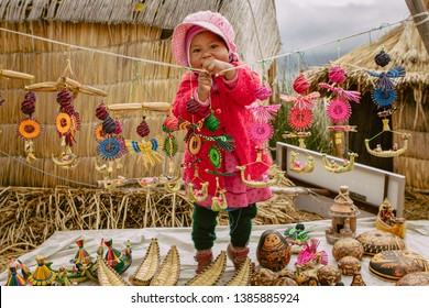 Beautiful girl trying to order the crafts to sell them. March 5, 2019, Island of the Uros, Puno, Peru.