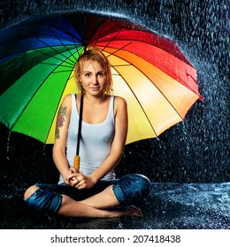 beautiful girl with umbrella under rain, black background