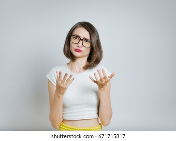 Beautiful girl unpleasantly surprised, does not know what to do, in confuses, with glasses isolated on a gray background