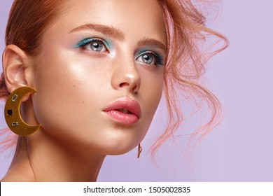 Beautiful girl with unusual accessories and make-up on a bright background. Beauty face. Photo taken in the studio