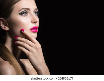 Beautiful girl with unusual black arrows on eyes and pink lips and nails. Beauty face. Picture taken in the studio on a black background.