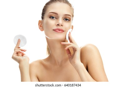 Beautiful girl using cotton pad. Portrait of smiling blonde cleaning skin by cotton pad. Skin care and beauty concept.