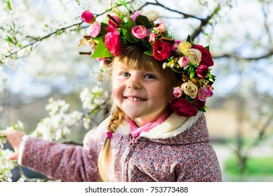 beautiful girl with a vein of flowers on her head walks in the spring in the park