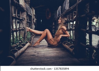 A beautiful girl in a vest and jeans shorts runs to the ocean, beautiful curly blond hair develops in the wind and she is happy, tenderness, sun, waves, pleasure and happiness, tan, skin, crazy Bali