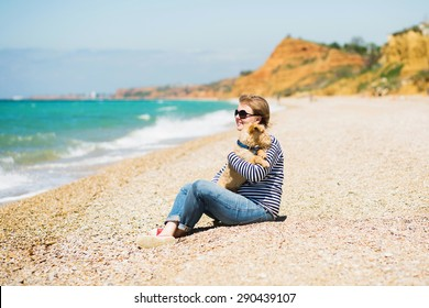 Beautiful girl in a vest sitting on the beach with a terrier puppy