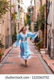 A beautiful girl in a vintage blue dress is running through the ancient streets of the old French town