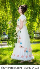 Beautiful girl in a vintage bride dress in a spring garden among the twig of a birch nestled with the beauty of nature and looking into the distance with hope and expectation.