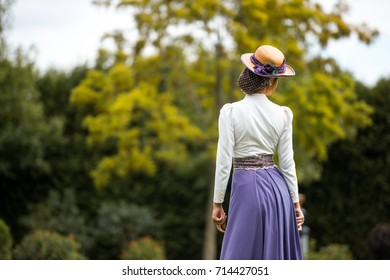 Beautiful girl in a vintage dress. Girl on a blurred background. A girl in a white blouse and a purple dress. A woman is dressed in retro style.