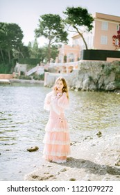 A beautiful girl in a vintage pink dress stands against the background of an ancient French town