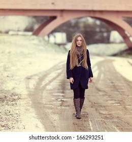 Beautiful girl walking along a winter road near the bridge. Portrait in full growth