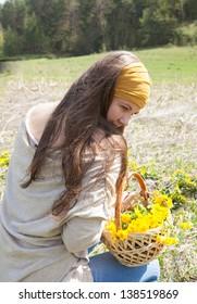 beautiful girl walking among yellow flowers outdoors