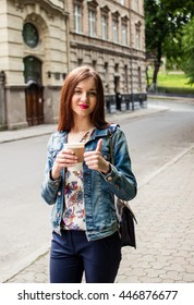 beautiful girl walking city and drinking coffee from paper cups
